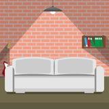 在砖墙背景的沙发 顶楼样式 免版税库存图片