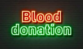 在砖墙背景的献血霓虹灯广告 免版税库存图片