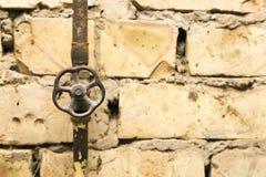 在砖墙背景的生锈的管道阀门 免版税库存图片