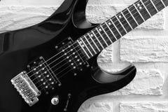 在砖墙背景的电吉他 免版税库存图片