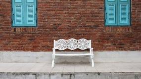 在砖墙背景的白色扶手椅子在蓝色窗口附近 库存照片