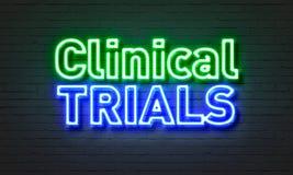 在砖墙背景的临床试验霓虹灯广告 免版税库存图片