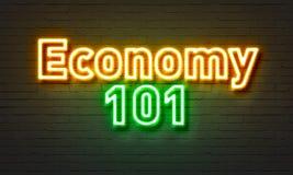 在砖墙背景的经济101霓虹灯广告 免版税图库摄影