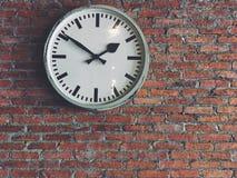 在砖墙背景隔绝的白色经典时钟吊 库存照片