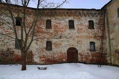 在砖墙附近在雪下的一条长凳在树附近 免版税库存图片