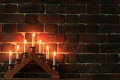 在砖墙附近的七烛台 免版税库存照片