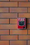 在砖墙黑色的火警 免版税图库摄影