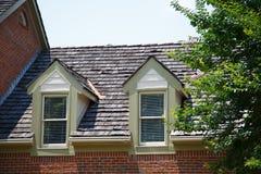在砖家的两个屋顶窗有木木瓦的 库存图片