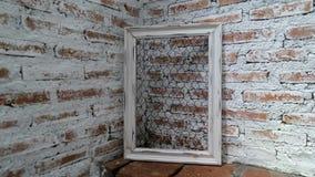 在砖展示墙壁上的白色框架在光下通过屋顶在屋子里 库存照片