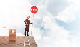 在砖房子屋顶陈列中止路标的白种人商人 混合画法 免版税库存照片