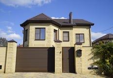 在砖房子的屋顶的装饰金属 篱芭由波纹状的金属制成 免版税库存照片