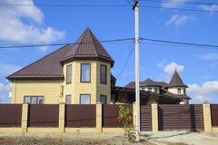 在砖房子的屋顶的装饰金属 篱芭由波纹状的金属制成 免版税图库摄影