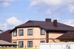 在砖房子的屋顶的装饰金属 篱芭由波纹状的金属制成 免版税库存图片