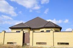 在砖房子的屋顶的装饰金属 篱芭由波纹状的金属制成 库存照片