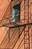 在砖瓦房外面的老,生锈的楼梯 免版税图库摄影