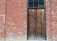 在砖瓦房的被风化的木门 免版税库存照片