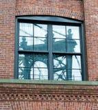 在砖瓦房窗口反映的曼哈顿桥梁 免版税库存照片