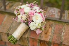 在砖的五颜六色的桃红色新娘花束 免版税库存图片