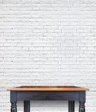 在砖的空的木葡萄酒桌铺磁砖墙壁,嘲笑为偏移 免版税库存图片