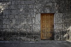 在砖石墙上的老木门作为背景 免版税图库摄影