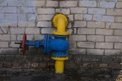 在砖磨房背景的消防龙头蓝色黄色红色 免版税图库摄影