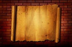 在砖背景的老纸张 库存照片