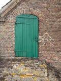 在砖谷仓的老绿色木门 库存照片