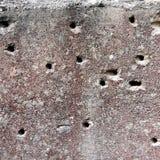 在破坏混凝土墙的孔,弹孔,抽象设计的背景自由空间在战争以后 免版税库存照片