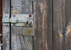 在破旧的木门背景的老生锈的金属挂锁 免版税图库摄影