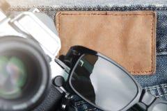 在破旧的牛仔裤的葡萄酒SLR照相机的构成和太阳镜在空白的皮革板材附近-旅行和博客作者概念-接近  免版税图库摄影