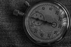 在破旧的牛仔裤背景,价值措施时间、老时钟箭头分钟和第二个准确性定时器纪录的秒表 图库摄影