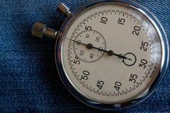 在破旧的老蓝色牛仔布背景、价值措施时间、老时钟箭头分钟和第二个准确性定时器纪录的秒表 免版税库存照片