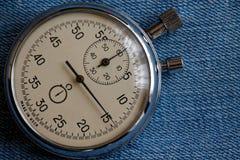 在破旧的蓝色牛仔裤背景,价值措施时间、老时钟箭头分钟和第二个准确性定时器纪录的秒表 免版税库存照片