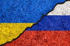 在破裂的墙壁和乌克兰的绘的旗子俄罗斯background/R上 库存图片
