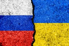 在破裂的墙壁和乌克兰的绘的旗子俄罗斯background/R上 免版税库存图片