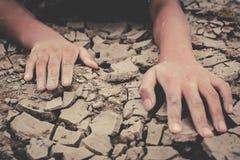 在破裂的干燥地面的人的手 免版税库存照片