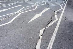 在破裂的沥青表面路的白色箭头 免版税库存照片