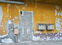在破裂的灰泥墙壁上的生锈的邮箱 免版税库存照片