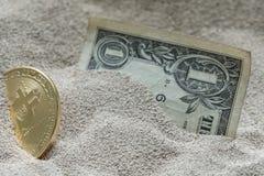 在硅沙子看部分地埋没的Bitcoin货币与一张一美元钞票一起 免版税库存图片