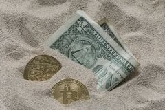 在硅沙子看部分地埋没的Bitcoin货币与一张一美元钞票一起 库存照片