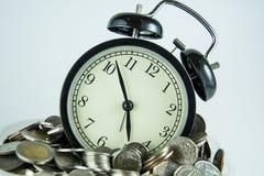 在硬币之间的闹钟 库存照片
