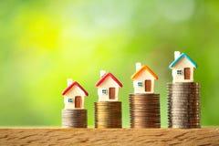 在硬币堆的四个微型房子模型在绿叶被弄脏的背景 库存照片