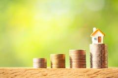 在硬币堆的微型房子模型在绿叶被弄脏的背景 免版税库存照片