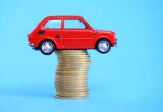 在硬币堆的红色微型汽车 免版税库存照片