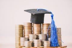 在硬币金钱的毕业帽子在白色背景 教育或奖学金概念的攒钱 免版税库存图片