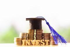 在硬币金钱的毕业帽子在白色背景 教育或奖学金概念的攒钱 免版税库存照片