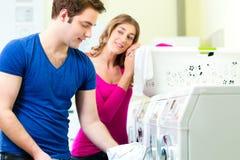在硬币洗衣店洗涤物的夫妇 库存照片