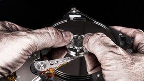 在硬盘驱动器的肮脏的手 艺术性的特写镜头,反映,黑背景 库存照片