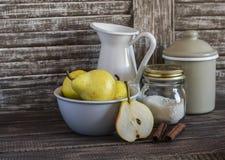 在碗、桂香、糖和葡萄酒陶器的新鲜的梨在黑暗的木背景 仍然厨房生活 库存照片