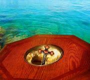 在碗叠加的耶稣受难象在湖前的洗礼盘 图库摄影